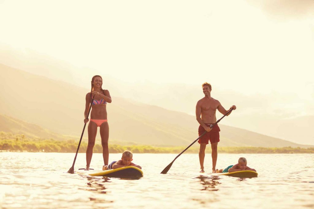 family paddling on sups